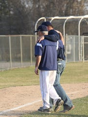 Eden Valley-Watkins Coach Mike Tomsche walks off the field with Jake  Foehrenbacher's father, Don, after throwing out the first pitch Thursday in Eden Valley.