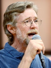 Phil Jamison calls a contra dance into the microphone