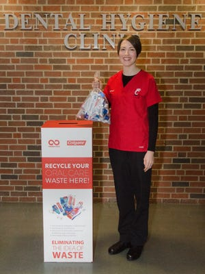 Dental hygiene student Suzanne Yorke at University of Cincinnati-Blue Ash shows off the recycling bin that is collecting dental waste as a fundraiser to help clinic patients.