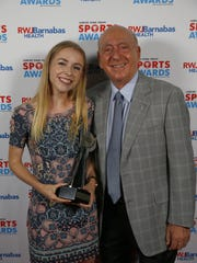 Howell outdoor track athlete Niamh Hayes takes a photo with guest speaker Dick Vitale.