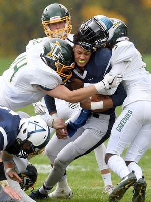 Asheville School's Ahmad Galimore loses his helmet as he gets taken down by Christ School's West Shuler, left, and Aydan White, right during the 91st meeting of the rival schools at Asheville School on Saturday, Oct. 28, 2017. The Greenies defeated the Blues 47-6.