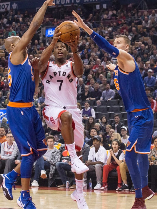 Toronto Raptors guard Kyle Lowry (7) drives to the net between New York Knicks forward Kristaps Porzingis (6) and guard Jarrett Jack (55) during first-half NBA basketball game action in Toronto, Friday, Nov. 17, 2017. (Chris Young/The Canadian Press via AP)