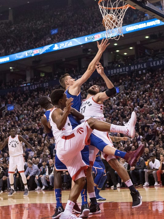 New York Knicks forward Kristaps Porzingis, center, takes a defensive rebound between Toronto Raptors guard Kyle Lowry, left, and center Jonas Valanciunas (17) during first-half NBA basketball game action in Toronto, Friday, Nov. 17, 2017. (Chris Young/The Canadian Press via AP)