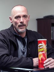 LMPD sergeant Paul Neal holds a Pringles can with a removable bottom that can be used to hide illegal drugs in plain sight. 3/21/18