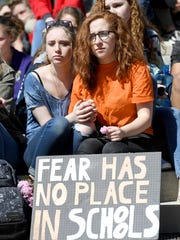Asheville High School freshmen Rowan Berry-Foster, left, and Ella Carlinnia, 15, listen to speakers during a national school walkout for gun reform at Pack Square Park on Friday, April 20, 2018.