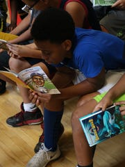 A young boy begins reading his new book during the