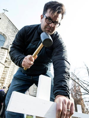 Josh McGee plants a cross on the front lawn of Highland Baptist Church as part of an annual event that pays tribute to homicide victims in Louisville. 12/7/14