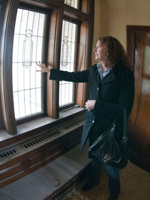 Jennifer Lehrke, architect and historic preservation consultant, looks through leaded glass windows at the 605 Erie preservation project.