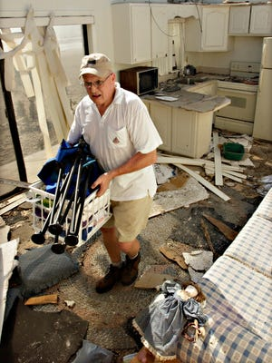 Tim McCoy salvages a tennant's belongings  at a Cocoa Beach  condo after Hurricane Frances in September 2004.
