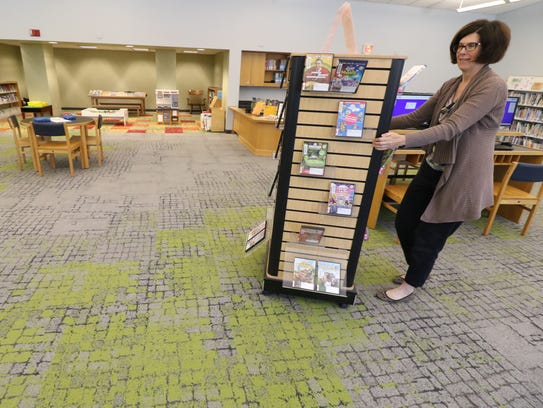 Library Director Nan Champe re-positions a display