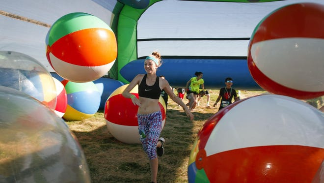 A participant maneuvers her way through one of 11 obstacles at the Insane Inflatable 5K at Hope Sports Complex in Lansing August 1.