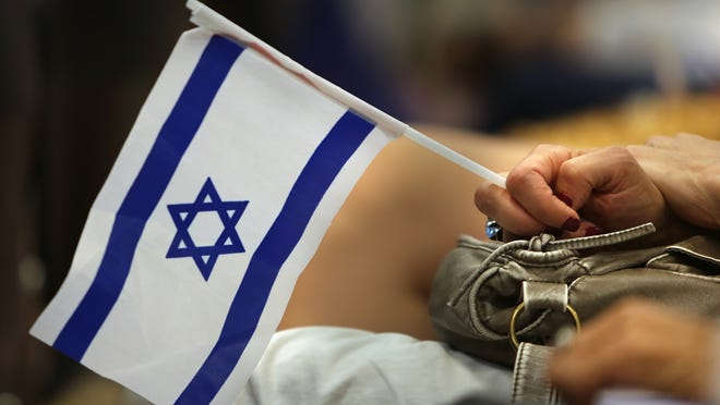 A woman holds an Israel flag at the Indianapolis Stands with Israel community gathering July 27, 2014, at the Arthur M. Glick Jewish Community Center.