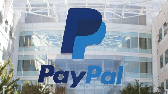 PayPal headquarters with PayPal logo displayed in front of large office building.