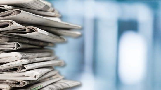 A stack of newspapers against blurred blue and white background.