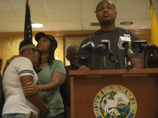 The sister of the late Antwan L Timbers Aniya Timbers (left) and his mother Angela Conner embrace  as his father Antwan Timbers  Sr. speaks at the podium during a press conference regarding the death of their love one, who was hit by an alleged drunk driver early Sunday morning.