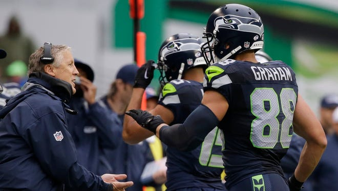 Seattle Seahawks head coach Pete Carroll, left, greets tight end Jimmy Graham (88) after a play against the Denver Broncos in the first half of a preseason NFL football game, Friday, Aug. 14, 2015, in Seattle.