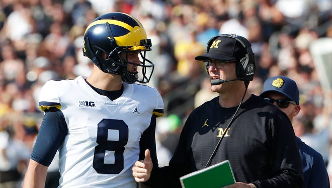 Sep 23, 2017; West Lafayette, IN, USA; Michigan coach Jim Harbaugh talks with quarterback John O'Korn during the game against Purdue at Ross-Ade Stadium.