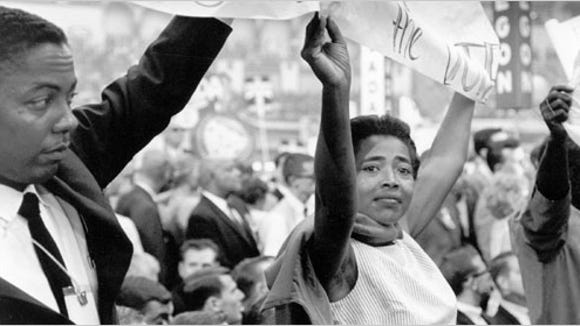 Victoria Gray, center, carries a banner as part of