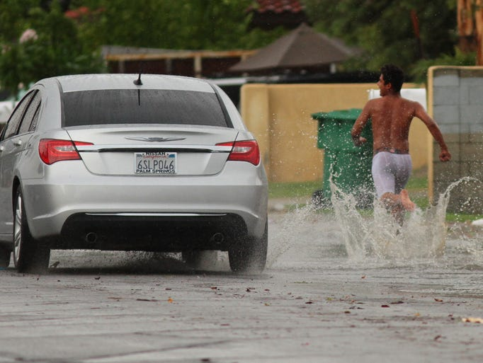 A young man runs barefoot through the water while racing a car down Wishing Well Trail in Cathedral City, Calif. as a storm rolls through the Coachella Valley on Sunday, August 3, 2014.