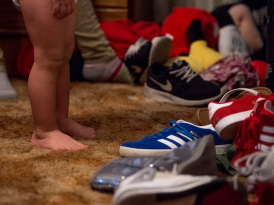"Vincent stands in front of a pile of shoes in Brooke's room while Brooke pulls out his clothes in the morning on Nov. 28, 2017. Even with the help of her father Michael, he says, ""it gets crazy sometimes. It makes me remember when [Brooke was] little, and what I had to do. And I get to show her and tell her, and try to teach her. That's just mind-numbing at times, because she's a teenager. It's a baby raising a baby."""