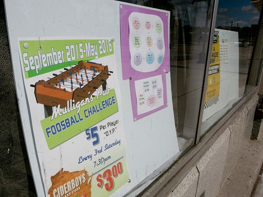 A flyer advertising the foosball challenge is displayed in the window at Mulligans Irish Pub in Wisconsin Rapids, Thursday, Sept. 3, 2015.