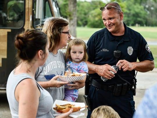 Marion police Officer Dave Dunaway chats with Marion residents in McKinley Park on Tuesday evening at one of the four stops Marion police officers made to hand out freeze pops and let community members and children explore their Tactical Response Vehicle. Police officers and the State of the Sandwich food truck visited four locations in Marion to give out free food.
