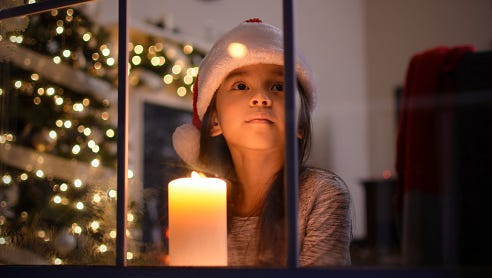 Little girl looking out the window on Christmas