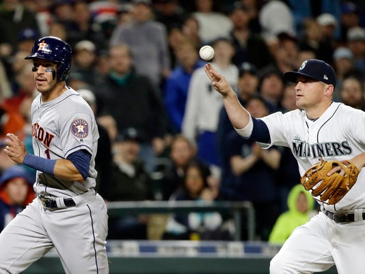 Seattle Mariners third baseman Kyle Seager, right, tosses the ball past Houston Astros' Carlos Correa during a rundown in the fourth inning of a baseball game Wednesday, April 12, 2017, in Seattle. Correa was out at home. (AP Photo/Elaine Thompson)