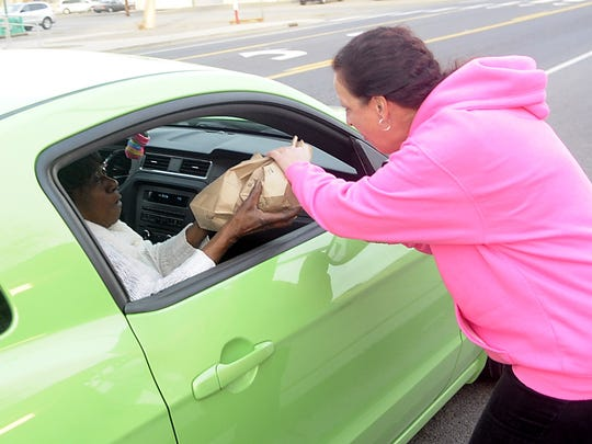 Yvonne Minix delivers an order to a customer in her car.