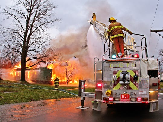 Amish firefighters train on the Ovid Fire Department's multipurpose fire truck during a live burn exercise in April 2014.