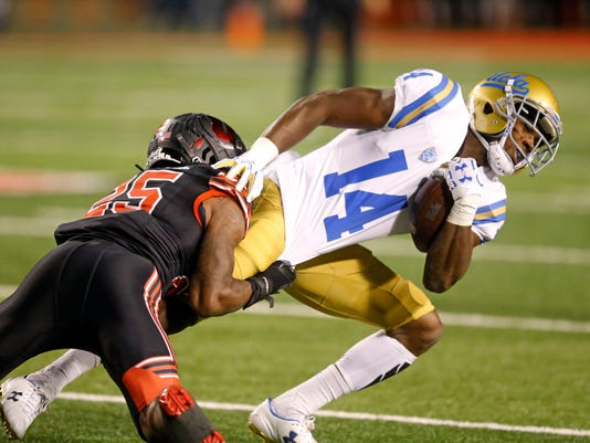 Utah defensive back Casey Hughes (25) tackles UCLA wide receiver Theo Howard (14) during the first half of an NCAA college football game Friday, Nov. 3, 2017, in Salt Lake City. (AP Photo/Rick Bowmer)