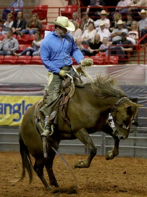 A cowboy competes in bronc riding Friday, Aug. 18, 2017, at the 37th annual Texas Ranch Roundup in Kay Yeager Coliseum.