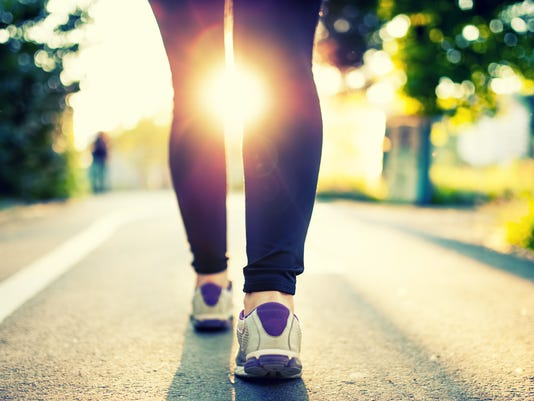 woman athlete feet and shoes while running in park.