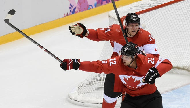 Canada forward Jamie Benn (22) celebrates with forward Corey Perry (24) after scoring a goal against USA in the second period in the men's ice hockey semifinals during the Sochi 2014 Olympic Winter Games at Bolshoy Ice Dome.