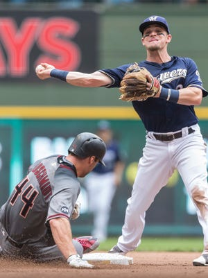 Milwaukee Brewers' Scooter Gennett gets the force out on Arizona Diamondbacks' Paul Goldschmidt while turning a double play getting Rickie Weeks Jr. out air first during the sixth inning of a baseball game Thursday, July 28, 2016, in Milwaukee.