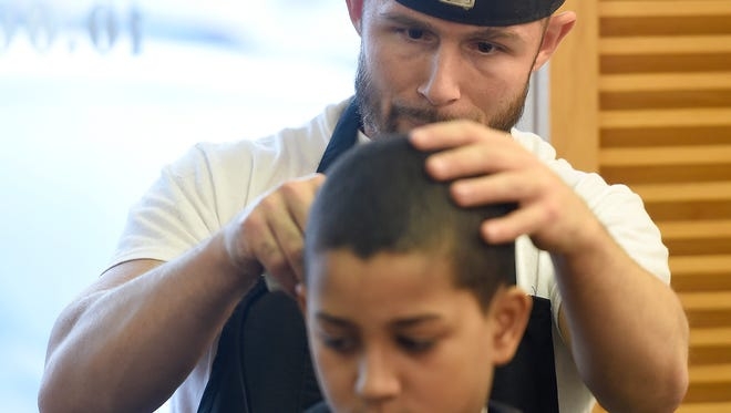 Izaiah Gonzalez, 11, has the official logo of the Denver Broncos cut into his hair by barber B.J. Read just intime for Super Bowl Sunday. On Sunday, Feb. 7, when the Denver Broncos and the Carolina Panthers go head to head two local Lebanon County kids will use their heads to support their favorite teams. Lebanon Barber Lounge's B.J. Read sculped the Bronco into Izaiah Gonzalez, 11. Barber Jose Calderon shaved the Panther on the head of Carmello Edwards, 6.