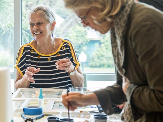 Elisa Austin laughs as she works on her seahorse resin window at the Arts in Medicine workshop June 21 at the Robert and Carol Weissman Cancer Center in Stuart.