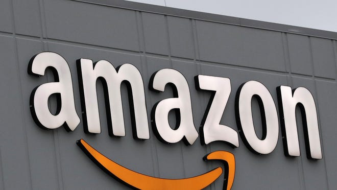 A sign is lit on the facade of an Amazon fulfillment center.