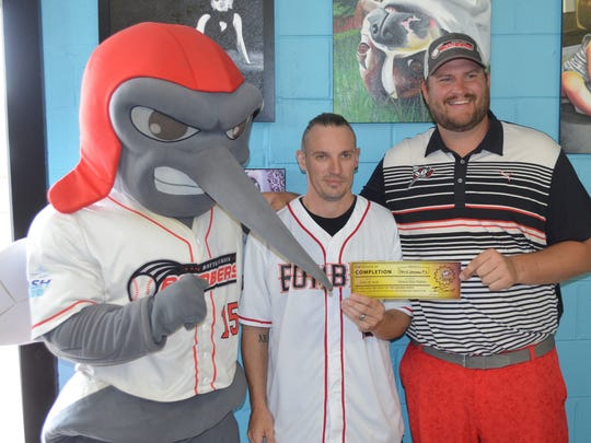 David Saxman gets his free Battle Creek Bombers tickets for life from General Manager Tyler Shore and Moe Skeeter.