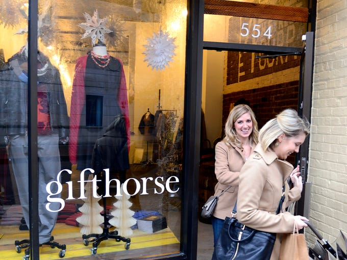 Customers Andolyn Johnson, left, and Holly Barger leave the Gifthorse after making several purchases. Co-owner Shawn Beirne displays a variety of shop-local holiday gifting selections from the Gifthorse store located in the South Fourth District. December 6, 2013