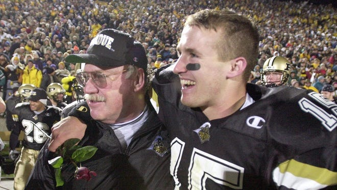 Purdue coach Joe Tiller and quarterback Drew Brees (15) leave the field after Purdue beat Indiana and clinched a Rose Bowl berth Nov.18, 2000.
