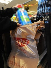 Courtesy clerk Cheryl Potter fills a customer's plastic bag purchased for 10-cents at Ralph's. Customers at checkout now have to pay 10-cents for a plastic or paper bag, or a $1.25 for a plastic re-useable bag.