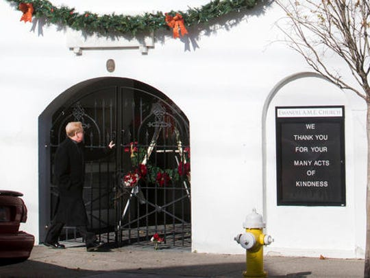 A man walks past flowers and a wreath at a door of Emanuel A.M.E. Church on Thursday, Dec. 15, 2016. Dylann Roof was convicted Thursday in the slaughter of nine black church members who had welcomed him to their Bible study at the church, a devastating crime in a country that was already deeply embroiled in racial tension.