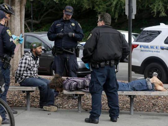 """Police officers arrest two men who attacked a student on the University of California, Berkeley campus in Berkeley, Calif., Thursday, Feb. 2, 2017. Jack Palkovic, a student wearing a """"Make America Great Again"""" hat, was attacked on the University of California, Berkeley campus a day after violent protests led authorities to cancel a controversial speech."""