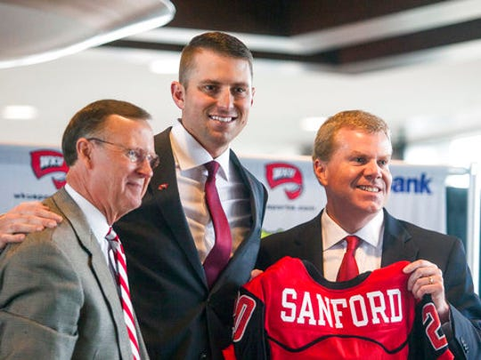 FILE - In this Dec. 14, 2016, file photo, Western Kentucky University president Gary Ransdell, left, new head coach Mike Sanford, center, and athletic director Todd Stewart pose for a photo during a news conference in Bowling Green, Ky. Five years as Western Kentucky's athletic director has yielded more success and trophies than Todd Stewart could have expected. The Hilltoppers have won 33 titles in 12 sports between two leagues over that span, including seven this past year in C-USA. (Austin Anthony/Daily News via AP, File)