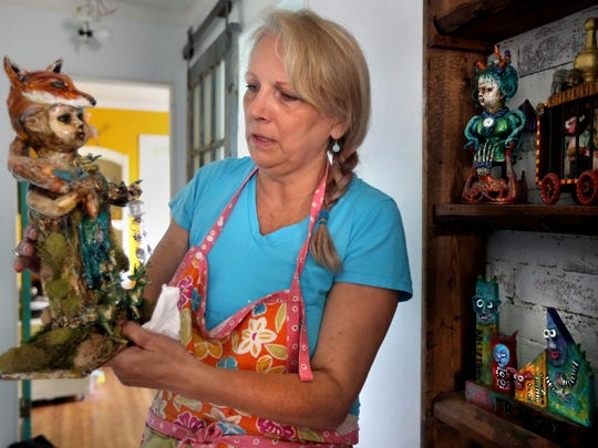 Dawna Magliacano, a local artist, shows off a piece of her mixed media artwork, created from found objects.