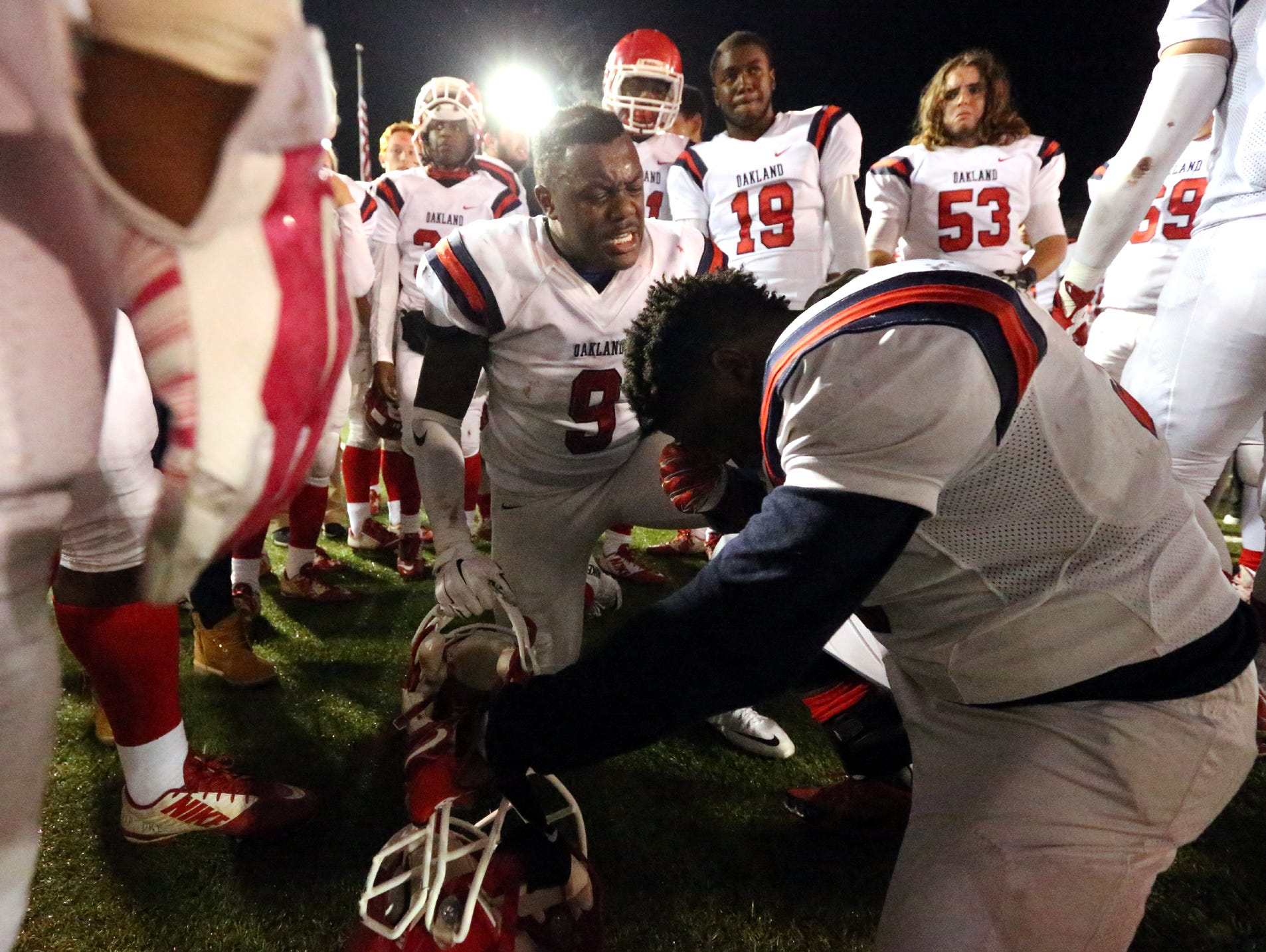 Oakland senior Ty Nix (9) encourages junior Chris Onwumere (99) after the Patriots' 27-13 loss in the semifinal playoff game to Maryville,
