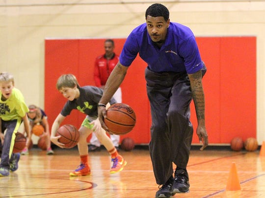Ed McCants performs a pass-through-the-legs drill along with students participating in the McCants Reality Basketball class held at the gym at the Marion County Children Services campus.
