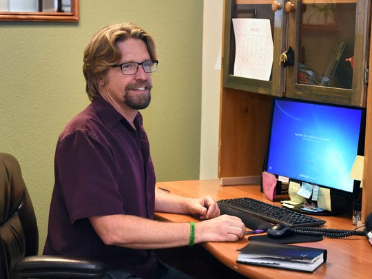 John Firestone sits at a desk at the The Life Change