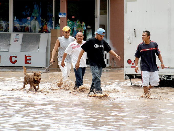 Residents trek through the muddy waters that flooded